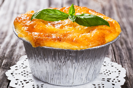 recipe decorated: French  cuisine- julienne. Mushroom, chicken and cheese gratin in Aluminum Foil Mini Baking mold decorated with basil leaves, on openwork napkin,  authentic recipe,close-up