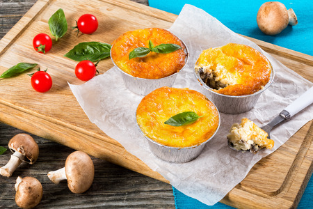 recipe decorated: Three portions of French julienne. Mushroom, chicken and cheese gratin in Mini Baking cups decorated with basil leaves on paper,One-Bite on spoon,  authentic recipe, top view Stock Photo