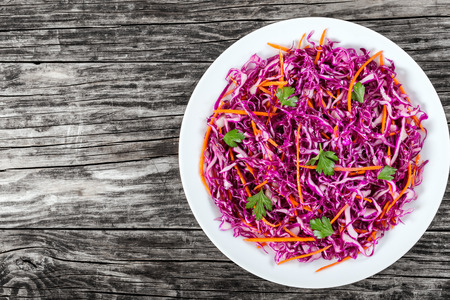 Salad coleslaw - red cabbage with carrots on white dish on old rustic boards, side dish, authentic classic recipe, view from above, blank space  for text left