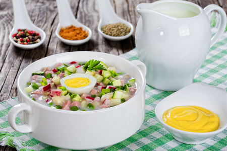 okroshka: meat, greens and vegetables cold summer soup with  serum and yogurt sprinkled with parsley and spting onion in white cup with spices and mustard in gravy boat on old rustic boards, view from above, close-up Stock Photo