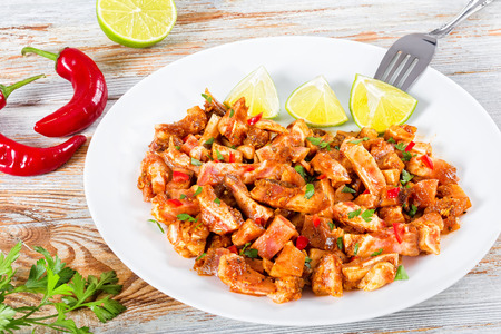 Braised Pig Ears or Oreja de Cerdo with spices,  chilli peppe, pices of lime sprinkled with parsley on white platter on natural wooden old boards, close-up, view from above Stock Photo