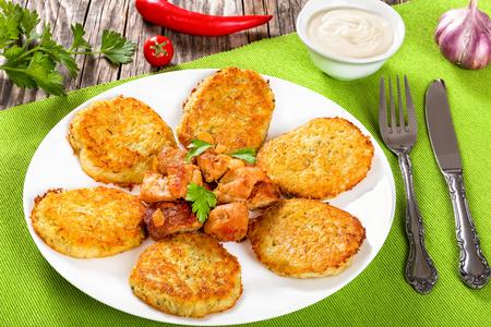 papas doradas: Crispiest destrozado de las croquetas de patata con carne frita y cebolla en la placa blanca en la estera de tabla, vista desde arriba, primer plano