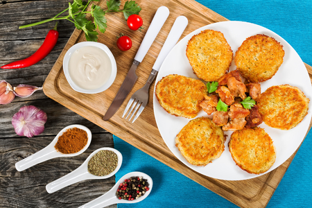 papas doradas: Crispiest Shredded Potatoes Hash Browns with fried meat and onion on white plate on cutting board on table mat, spices in porcelian spoons on wooden table, view from above