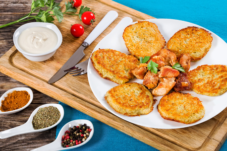 papas doradas: Crispiest Shredded Hash Browns with fried meat and onion on white plate on cutting board on table mat, spices in porcelain spoons on wooden table, view from above, close-up