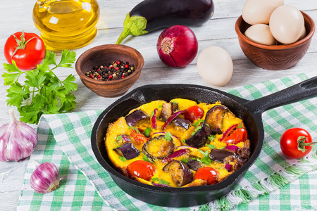 scrambled eggs, eggplant, onion and tomato in frying pan on kitchen towel,  garlic, aubergine,egg, olive oil, parsley and ripe tomatoes on wooden boards, view from above, close-up
