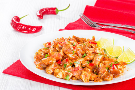 cooked and marinated Pig Ears or Oreja de Cerdo with spices, chili pepper, pieces of lime sprinkled with parsley on white platter on wooden old boards, top view Stock Photo
