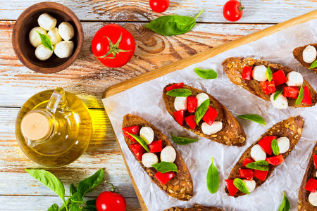 bruschetta with tomatoes, mini mozzarella and basil on fried in olive oil rye baguette with seeds, bottle with oil, tomatoes and mozzarella in small bowl, herbs on peeling paint  planks, top view