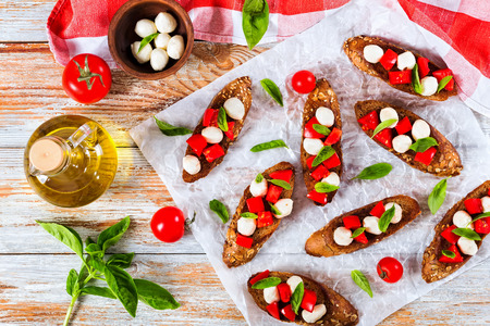 bruschetta with tomatoes, mozzarella and basil on fried in olive oil rye baguette with seeds, on parchment paper. ingredients on peeling paint white planks, italian recipe,top view