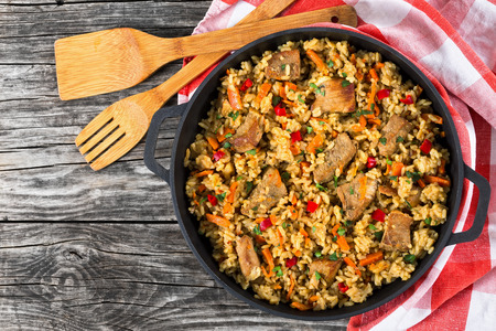 Homemade prepared paella with meat, pepper, vegetables and spices in iron pan with kitchen towel on wooden table, copy space left,  view from above