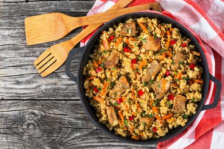 Selbst gemachte zubereitet Paella mit Fleisch, Paprika, Gemüse und Gewürze in Eisenpfanne mit Küchentuch auf Holztisch, Kopie Raum links, von oben Standard-Bild - 64036361