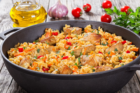 Homemade prepared paella with meat, pepper, vegetables and spices in iron stewpan on wooden planks, bottle of olive oil,tomatoes, parsley, garlic on background, close-up, view from above