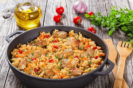 Selbst gemachte zubereitet Paella mit Fleisch, Paprika, Gemüse und Gewürze in Eisen stewpan auf hölzernen Planken, eine Flasche Olivenöl, Tomaten, Petersilie, Knoblauch auf den Hintergrund, close-up, Ansicht von oben Standard-Bild - 64036360