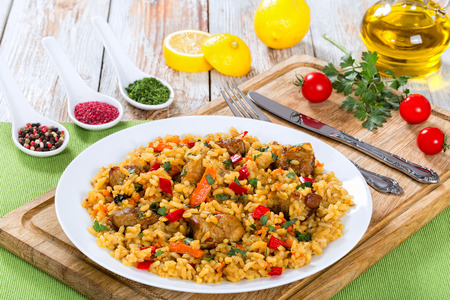 tasty paella with meat, pepper, vegetables and spices on platter on cutting board, lemon slice, spices and cherry tomatoes on background, view from above, close-up Stock Photo