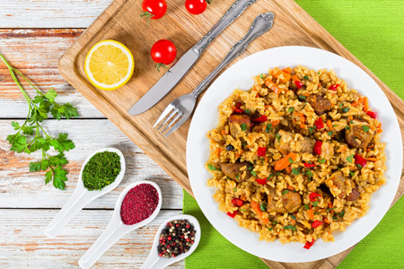 rice with meat, pepper, vegetables and spices on dish on cutting board, lemon slice, spices and cherry tomatoes on background, view from above