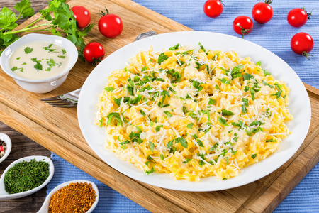 Fettuccine Alfredo served in a sauce of cream, butter, and grated Parmesan cheese, sprinkled with parsley on white dish on cutting board, view from above, close-up Stock Photo