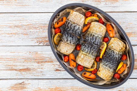 rolls-up of fillet of mackerel  with grilled carrots, cherry tomatoes and lemon in baking dish, on white peeling paint table, view from above
