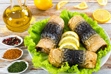 healthy baked fillet of mackerel on lettuce leaves and lemon slices on white platter. bottle with olive oil and ceramic spoons with spices on white peeling paint planks,  close-up