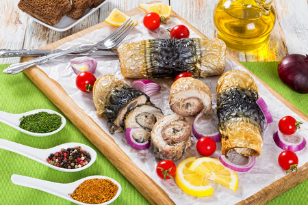 healthy baked fillet of mackerel in rolls, tomatoes and lemon slices on white parchment paper on cutting board with fork and knife, spices, rye bread and bottle of olive oil on background, close-up