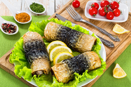 healthy baked fillet of mackerel in rolls on lettuce leaves and lemon slices on white dish on cutting board with fork and knife, spices and plate with cherry tomatoes on background, close-up Stock Photo