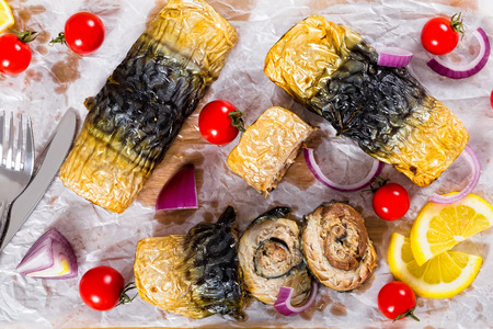 healthy baked fillet of mackerel in rolls on white parchment paper with fork and knife,onion, tomatoes, and lemon slices on background,view from above
