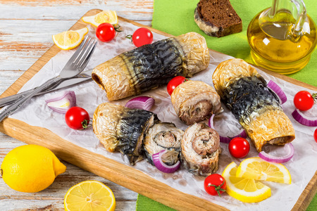 healthy baked fillet of mackerel in rolls, tomatoes and lemon slices on white parchment paper on cutting board with fork and knife,onion and bottle of olive oil on background, top view