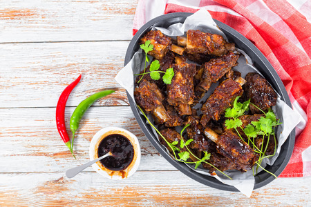 roasting pan: delicious hot sticky ribs seasoned with a spicy garlic ginger barbecue sauce amd cilantro in oval roasting Pan on white planks. green and red chili peppers on background, top view
