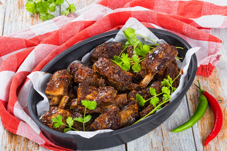 roasting pan: delicious hot sticky ribs seasoned with a spicy garlic ginger barbecue sauce and cilantro in oval roasting pan on white planks with kitchen cloth. green and red chili peppers on background, close-up Stock Photo