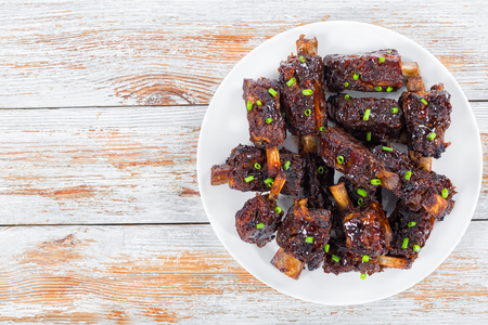 marinade: fried sticky ribs marinated in soy sauce and ginger sprinkled with green onion on white dish  on peeling paint wooden boards, view from above Stock Photo