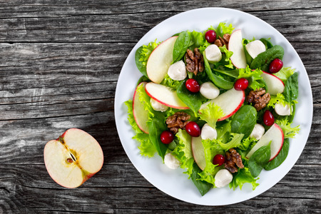 delicious autumn vitamins vegetarian salad: apple, spinach, mini mozzarella balls, lettuce, walnuts, cranberry on white dish  on old dark rustic boards, copy space left, view from above