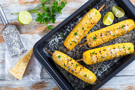 sprinkled: Grilled corn on cob sprinkled with parsley and grated parmesan, lime slices in roasting dish on white peeling paint table with grater and piece of cheese on parchment paper, top view, close-up Stock Photo