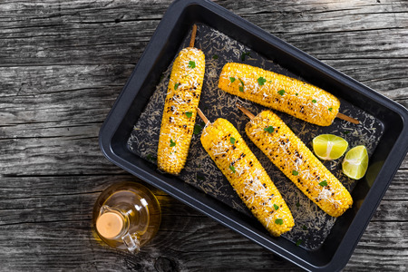 Grilled corn on cob sprinkled with parsley and grated parmesan cheese and lime slices in roasting dish on old wooden planks,  bottle with olive oil on background , top view Stock Photo