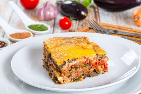 Portion köstlicher Moussaka mit Petersilie für authentisches Rezept gekocht, auf Tellern, auf weißen Peeling-Farbtafeln Standard-Bild - 65575661