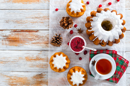 delicious  rum bundt cake with sugar glaze and cranberry on parchment paper with cup of tea on table napkin, cranberry jam,  pinecones on white peeling paint wooden background, view frrom above