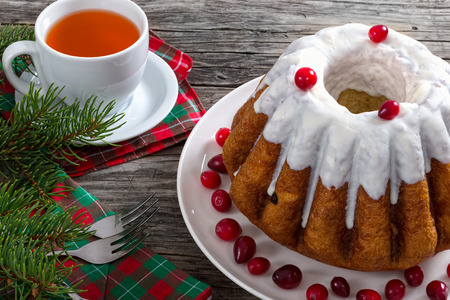 recipe decorated: delicious  rum bundt christmas cake with sugar glaze and cranberry on white dish with cup of tea and dessert forks on table napkins on old wooden background, view frrom above, close-up