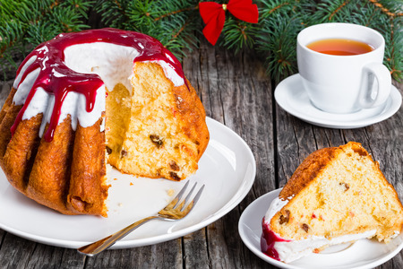delicious rum bundt christmas cake with red and white sugar glaze dripping on white dish with dessert forks, piece of cake on plate,. spruce branches and cup of tea on old wooden background,  close-up Stock Photo