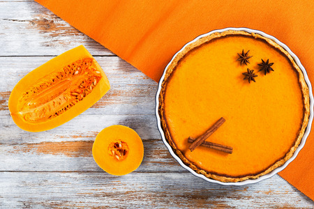 delicious Fresh round bright orange homemade pumpkin pie decorated with anise stars in baking dish on white table with half of squash on background, authentic recipe, view from above