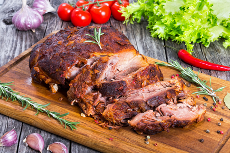 Big Piece of Slow Cooked Oven-Barbecued Pulled Pork shoulder on chopping board with mixed peppercorns, rosemary and garlic, tomato and lettuce salad on background, view from above, close-up