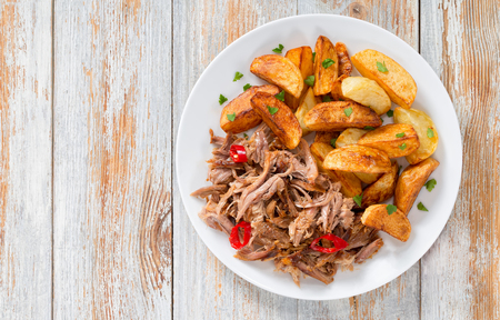 portion of pulled slow-cooked delicious meat roasted in oven with fried potato wedges sprinkled with parsley on white plate with spices and chili  on old wooden table, top view