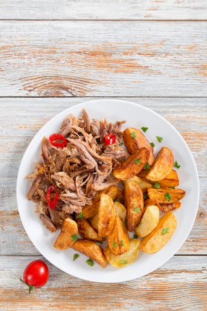 portion of pulled slow-cooked delicious meat roasted in oven with fried potato wedges sprinkled with parsley on white plate with spices and chili  on old wooden table, vertical top view Stock Photo
