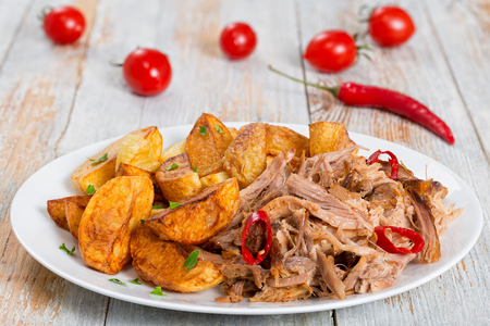 pulled slow-cooked pork shoulder grilled in oven with fried potato wedges, chili pepper and spices on white peeling paint wooden table, view from above,close-up