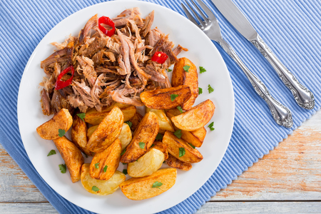 pulled slow-cooked pork shoulder grilled in oven with fried potato wedges, chili pepper and spices on lilac table mat with fork and knife, on wooden table, view from above