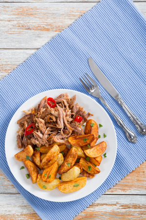 pulled slow-cooked pork shoulder grilled in oven with fried potato wedges, chili pepper and spices on lilac table mat on white peeling paint wooden table, vertical view from above