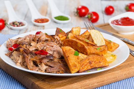 pulled slow-cooked pork shoulder grilled in oven with fried potato wedges on white plate  with tomato sauce on chopping board on wooden table, close-up