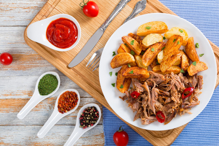 pulled slow-cooked pork shoulder grilled in oven with fried potato wedges on white plate  with tomato sauce on chopping board on wooden table,view from above