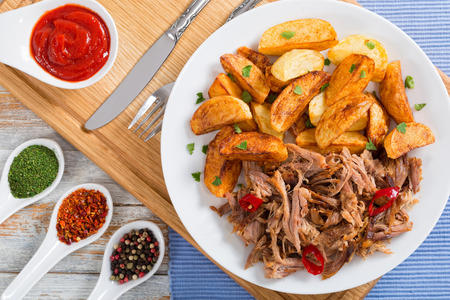 pulled slow-cooked pork shoulder grilled in oven with fried potato wedges on white plate  with tomato sauce on chopping board on wooden table, close-up, top view