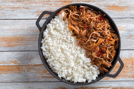 pulled slow-cooked pork shoulder grilled in oven with basmati rice in iron frying pan on wooden table, view from above Stock Photo