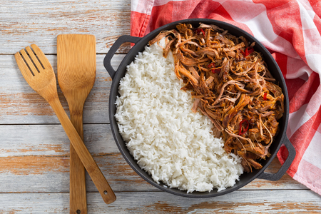 pulled slow-cooked pork shoulder grilled in oven with long-grain basmati rice in iron stewpot with kitchen towel, on wooden table, view from above