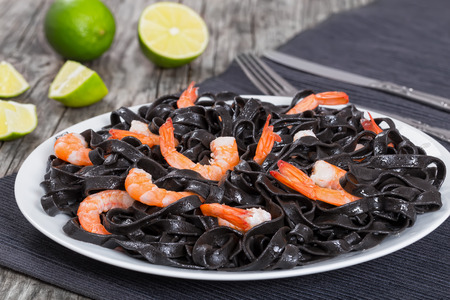 delicious squid ink black noodles with shrimps on white dish on grey table mat with fork and knife, on old wooden planks with pieces of lime on background, easy recipe, close-up