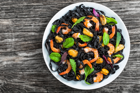 mussel: seafood black noodles salad with prawns, mussels, fresh green spinach, lettuce, arugula and mint on white dish on dark wooden table, view from above Stock Photo