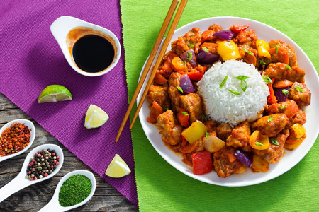 rice with Sweet and Sour fried pork chunks with vegetables, sprinkled with green onion on white dish on dark wooden background with soy sauce, spices and slices of lime, view from above, close-up